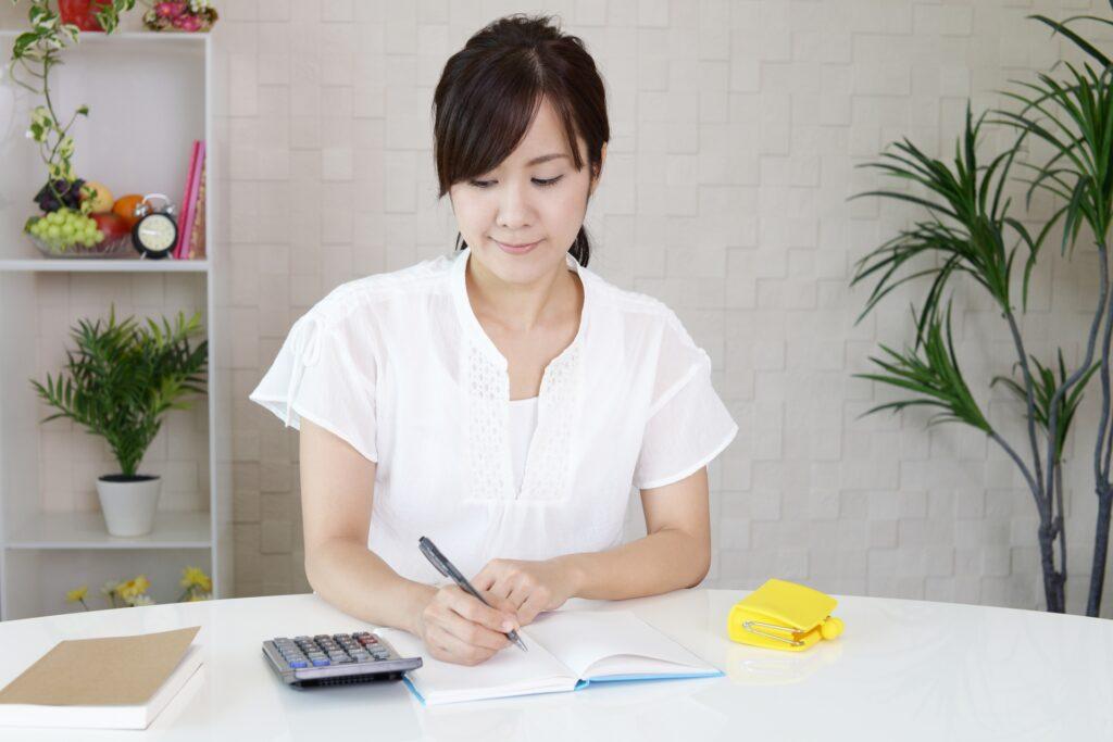 家計節約の計算をする主婦