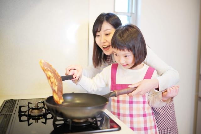 ガスを使っって調理中の母と娘